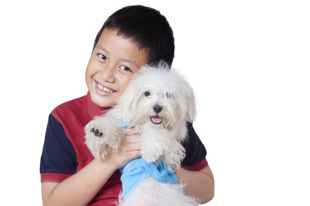 asian boy: Photo of a cheerful little boy smiling at the camera while embracing a maltese dog in the studio, isolated on white