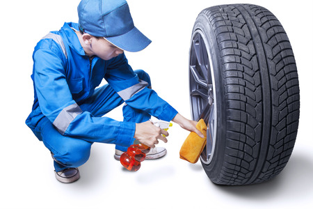 water vehicle: Young mechanic wearing blue uniform clear a wheel with a spray and cloth, isolated on white background