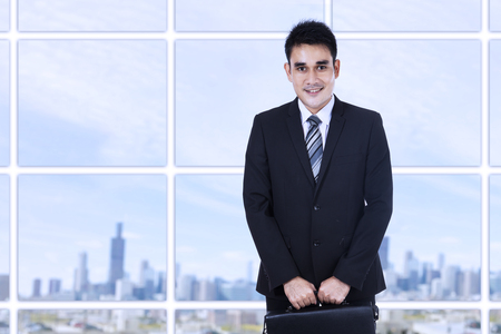 standing businessman: Portrait of young businessman standing in the office with a briefcase
