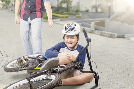 asia children: Little boy gets accident on the road with his bicycle and crying, dad coming to help