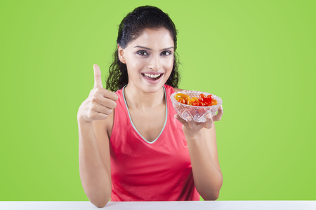 yummy: Healthy indian woman holding a bowl of tomato while showing thumb up on the camera, shot in the studio
