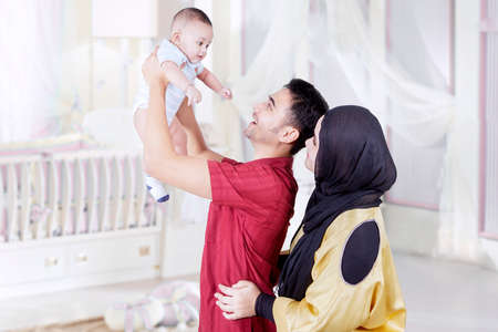 muslim baby: Young father lifting his baby with his wife standing in the bedroom together, shot at home
