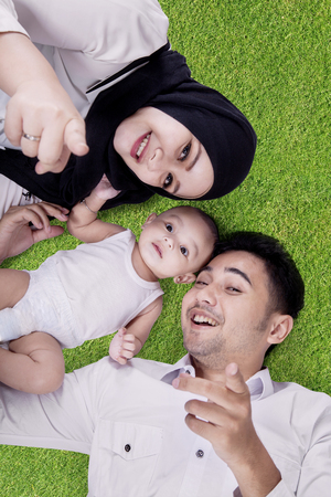 parents with baby: Two happy young parents lying on green grass with their baby and smiling at the camera together Stock Photo