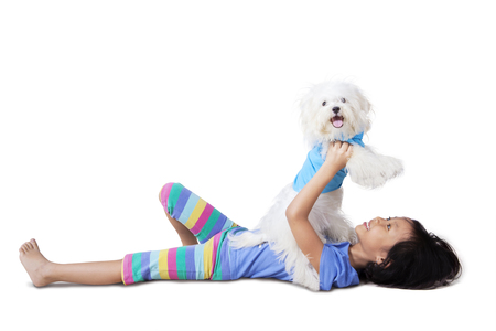 girl lying: Photo of cheerful little girl lying on the floor while playing with her puppy Stock Photo