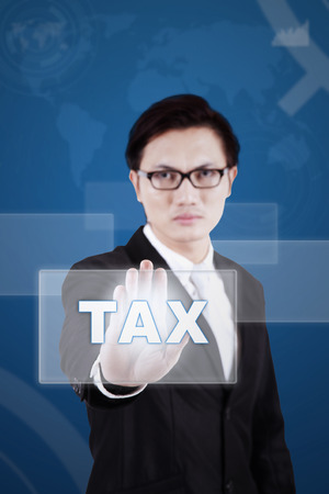 chinese businessman: Young chinese businessman touching a tax button on the modern futuristic screen