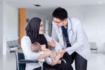 arabic: Portrait of a young mother and her baby helped by doctor to stand from wheelchair in the hospital lobby Stock Photo