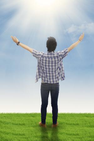 alabando a dios: Vista trasera de un joven de pie en el prado con las manos extendidas y disfrutar del aire fresco