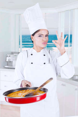 chef cocinando: Portrait of indian female chef showing ok sign while holding pan and standing in the kitchen