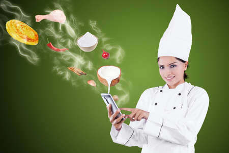 internet search: Portrait of beautiful female chef using a smartphone for searching recipe online