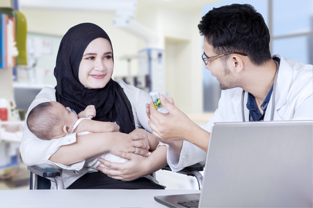 doctor with pills: Male pediatrician explaining drugs to a young mother with her baby in the clinic