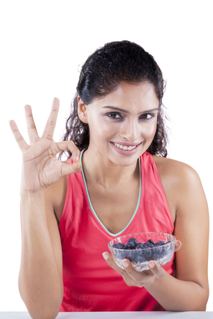 good food: Indian young woman showing OK sign while holding a bowl of blueberry and smiling at the camera Stock Photo