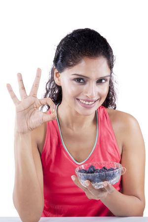 comida rica: mujer joven india que muestra signo de OK mientras sostiene un tazón de arándanos y sonriendo a la cámara