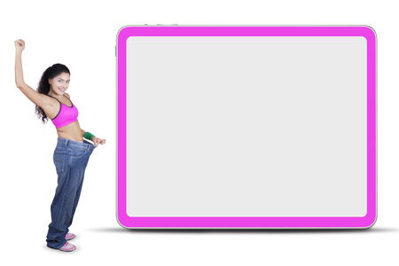 slim woman: Successful Indian woman lose weight and wearing old pants near the empty whiteboard Stock Photo