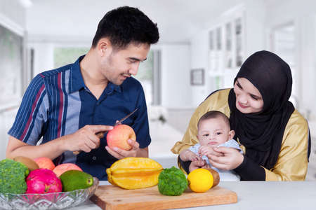 middle eastern families: Young man peels a fresh apple in the dining room for his wife and baby