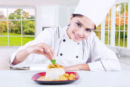 chefs: Portrait of a young female chef garnishing food in the kitchen