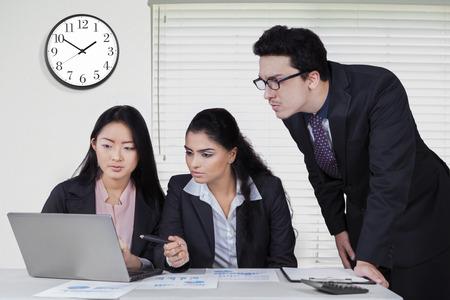 jovenes empresarios: Tres j�venes empresarios que llevaban traje formal y el uso del ordenador port�til en la oficina con un reloj en la pared