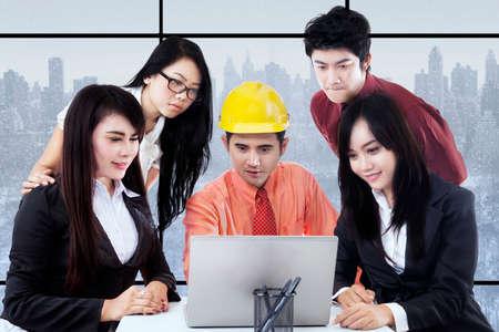 jovenes empresarios: Grupo de j�venes empresarios y arquitecto en una reuni�n de negocios, mirando el ordenador port�til