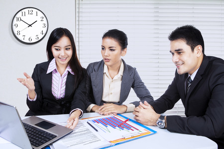 asian group: Picture of beautiful female entrepreneur explaining business plan to her partners with laptop computer in the office
