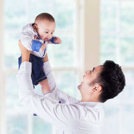 adult family: Portrait of cheerful dad lift up his male infant near the window at home