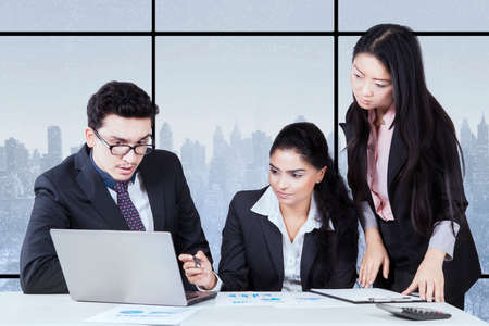 mixed race people: Picture of three young mixed race businesspeople having discussion in the office and using laptop computer