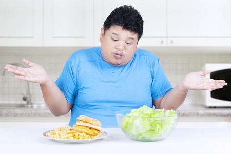 eating salad: Picture of fat person sitting in the kitchen and looks confused to choose hamburger or salad