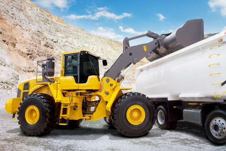 industrial machinery: Image of a yellow backhoe loading a mine with a scoop into the truck at mining site Stock Photo
