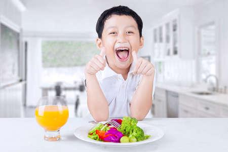 plato del buen comer: Fotografía de un niño pequeño alegre que muestra signo de OK con un plato de ensalada de verduras y el jugo sobre la mesa en casa