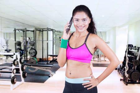 ejercicio aeróbico: Retrato de la mujer india vestida con ropa deportiva y hablando por teléfono en el gimnasio