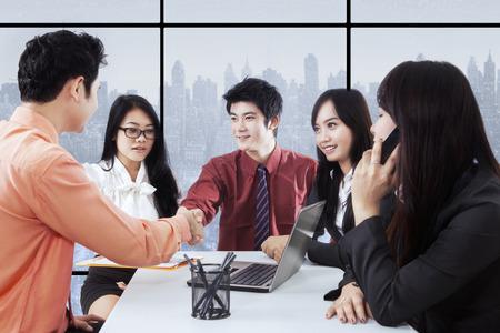 jovenes empresarios: Grupo de cinco jóvenes empresarios exitosos de cerrar un acuerdo para estrechar la mano en la oficina