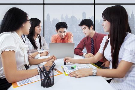 jovenes emprendedores: Imagen de cinco jóvenes empresarios discutiendo en la oficina con el ordenador portátil y documentos Foto de archivo