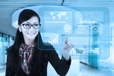 accessing: Portrait of young businesswoman using a virtual screen to make business solutions and accessing financial statistics