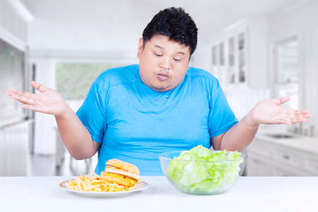 choose person: Portrait of overweight person looks confused in the kitchen to choose hamburger or salad