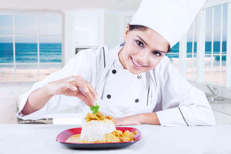 garnishing: Portrait of young indian chef woman decorating delicious food in the kitchen