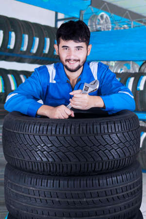 car part: Photo of middle eastern wearing uniform and holding wrench, smiling at the camera in the tire store Stock Photo