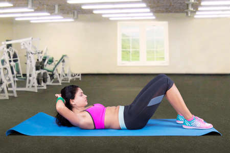 situp: Attractive indian woman workout in fitness center and doing sit-up on a mattress Stock Photo