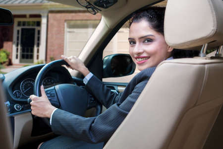 indian women: Successful indian businesswoman driving new car and smiling at the camera