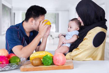 convivencia familiar: Padre joven que juega con su bebé utilizando dos frutas de color naranja en los ojos, lanzó en el país