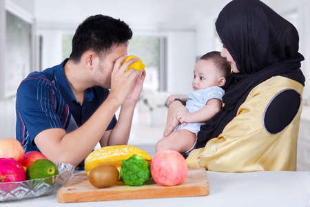 family life: Young father playing with his baby using two orange fruit on his eyes, shot at home