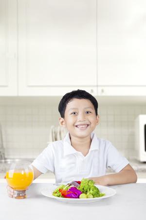 niños comiendo: El niño pequeño feliz sonriendo a la cámara mientras mantiene un vaso de zumo de naranja en la cocina con ensalada de verduras en la mesa