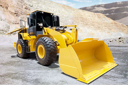 backhoe loader: Image of a big wheel loader with yellow color and a big scoop on the mining site