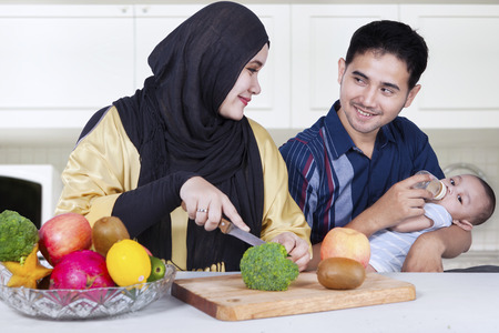 muslim baby: Muslim parents and their baby cutting broccoli and fruits to make healthy food in the kitchen Stock Photo