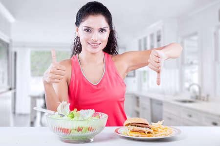 personas comiendo: Hermosa mujer india que se sienta en la cocina y que muestra el pulgar hacia arriba en la ensalada y el pulgar hacia abajo en la hamburguesa