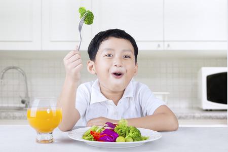 plato del buen comer: Fotografía de un niño pequeño que se sienta en la cocina y se come ensalada de verduras con jugo de naranja