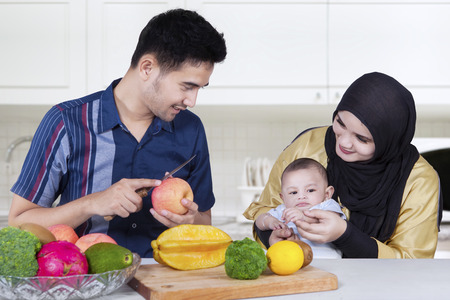 middle eastern families: Middle eastern father smiling at his wife and baby while peeling apple in the kitchen