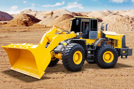 gravel: Image of a big wheel loader with yellow color and a scoop on the mining site