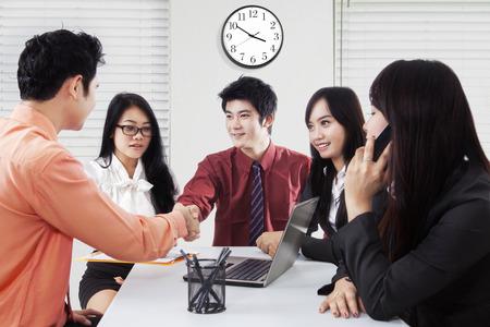 cerrando negocio: Imagen de dos hombres administradores cierre de una reunión de negocios dando la mano delante de sus empleados, un disparo en la oficina