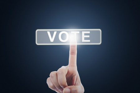 touch screen: Image of hand touching virtual screen with a vote button. Election concept Stock Photo