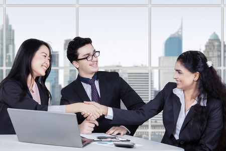deal in: Two multi ethnic businesswomen shaking hands closing a deal in front of a businessman at workplace
