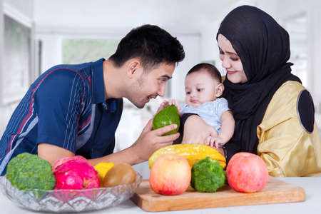 arabian food: Portrait of happy Arabian father giving a fresh fruit to his son at home