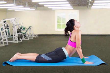 bhujangasana: Young indian woman exercising cobra yoga pose in fitness center Stock Photo